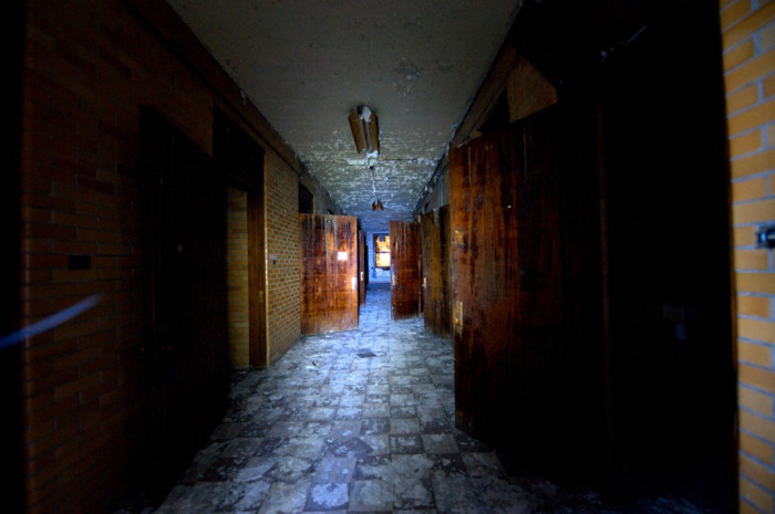 This photos captures looking down a hallway full of opened doors at an abandoned insane asylum.