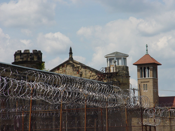 4) The walls surrounding the prison are 24 feet high and 6 feet wide at the base, with foundations that are 5 feet deep.