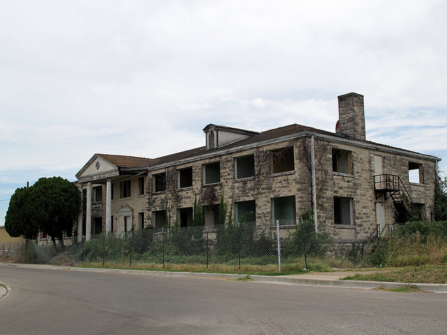 8) What might have been a sprawling mansion or apartment building in Waco is now a defunct skeleton, covered in ivy and moss.