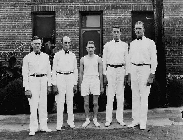 9. 1920's, a group of men pose for a picture.