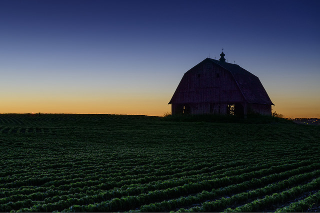 15. At the end of the day, an old barn in rural Iowa watches the sun drop down over the perfect green fields.