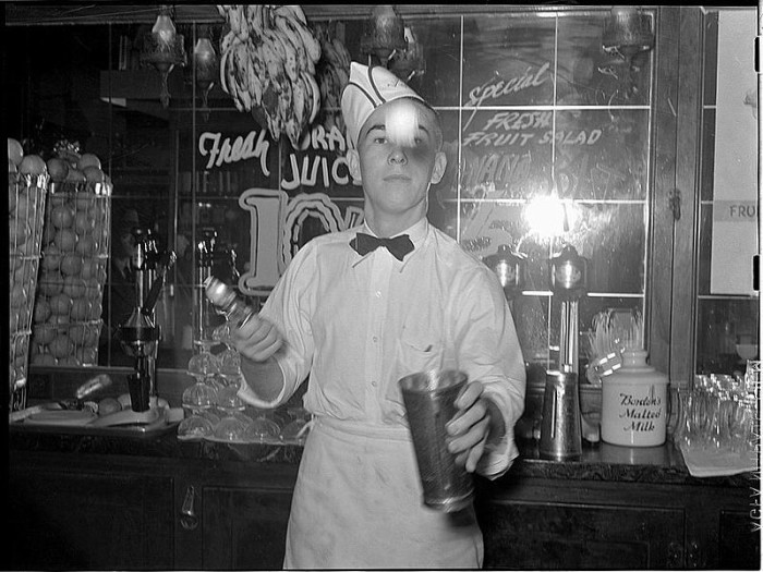 15) A soda jerker tossing a scoop of ice cream into a metal mixing cup before blending a shake in Corpus Christi in 1939. Oh, the good ol' days..
