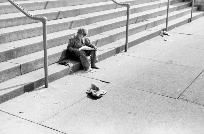 13. Boy reading the comics on the steps of the Milwaukee public library, circa 1940.