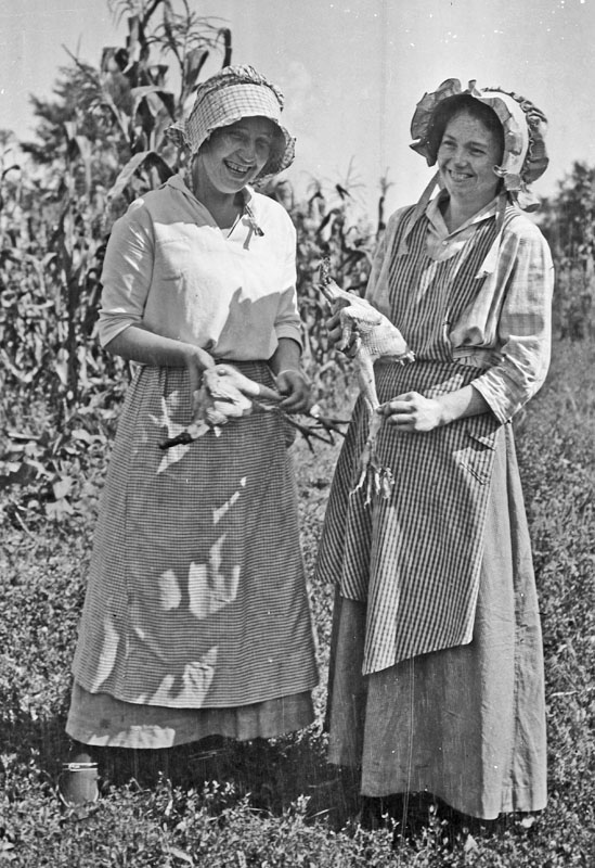 """12. These two Iowa farm women exchanging """"why did the chicken cross the road"""" jokes as they pluck feathers in 1917."""