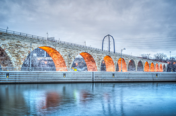 8 Stone Arch Bridge lit up on a cloudy morning.