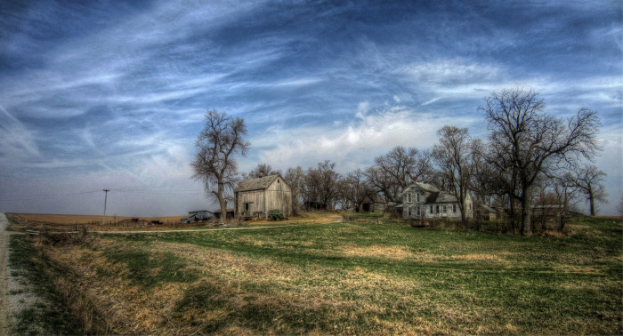 An Older Farmhouse Peeking Out From Behind Trees Near Omaha