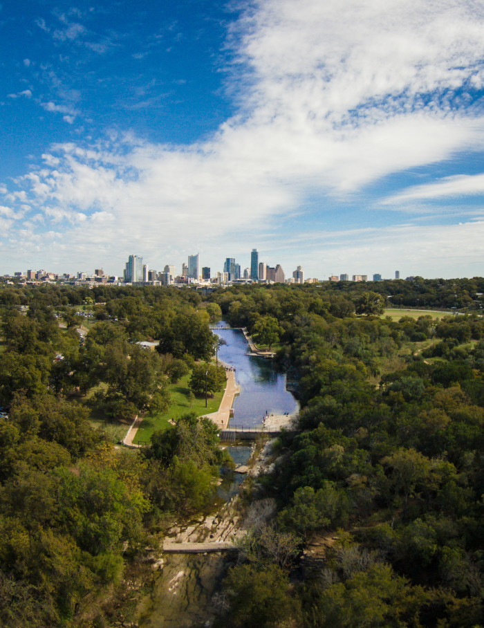 12) Barton Springs Pool surrounded by Zilker Park in Austin, with the city skyline as the backdrop. Texas is beautiful!