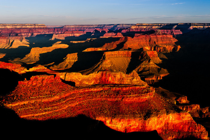 16. The Grand Canyon looks red and dramatic as the sun's angle moves up the sky.