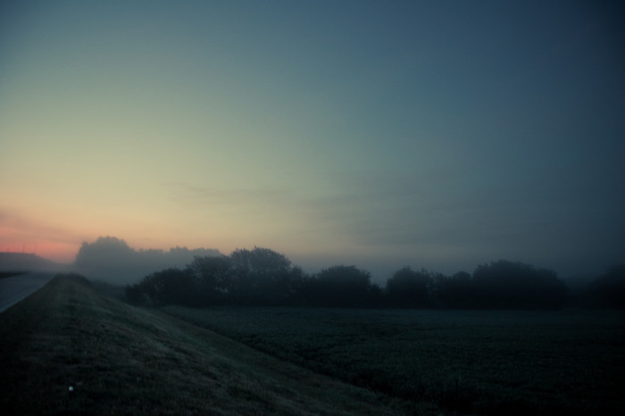 Misty sunrise hills and trees greet an early morning traveler in Greenwood.