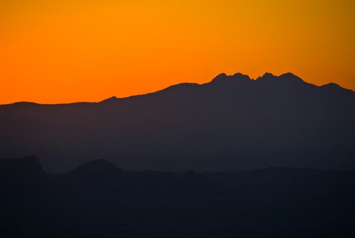 6. The Four Peaks shows off its curves against an orange sky just before sunrise.