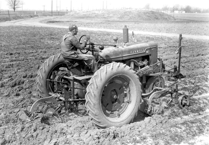6. Hard at work on a tractor at a Stoneville farm.