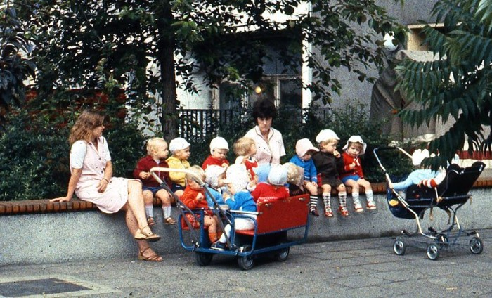 800px-East_Berlin_childminders,_with_children_and_strollers,_seated_on_a_wall,_1984