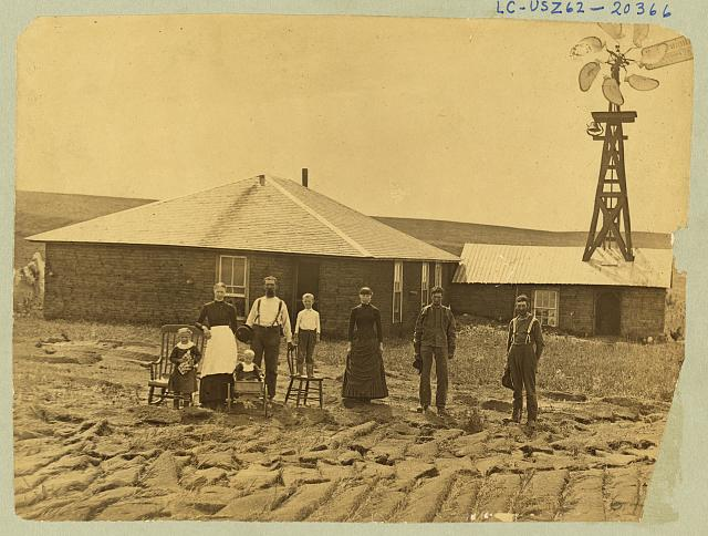 A Family in Front of Their Sod House (Complete With a Windmill on the Roof of an Outbuilding), Coburg, 1884 or 85