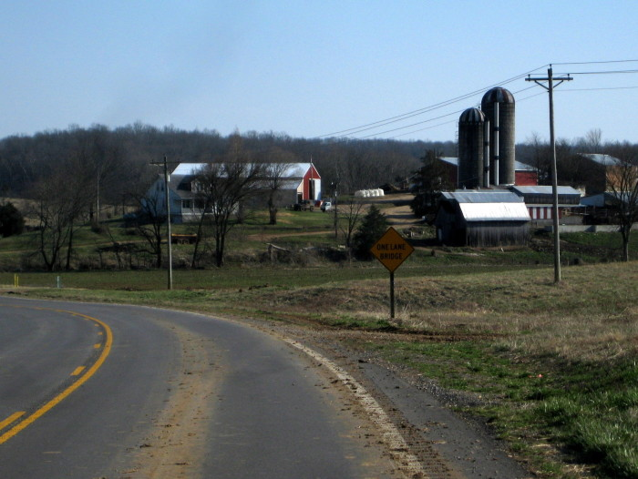 12. Wonderful capture of all the farm buildings, road and even a sign warning of a one lane bridge ahead.