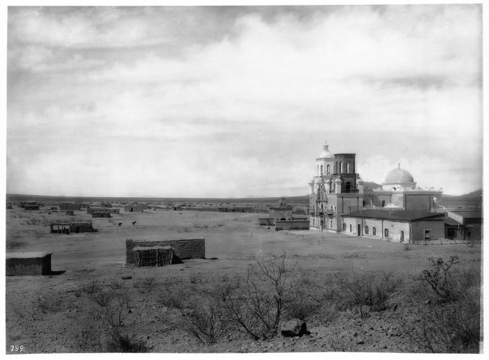 13. This image of Mission San Xavier del Bac was taken between 1898 and 1900. It features small homes of local Tohono O'odham families south of the mission but not much else in way of structures.