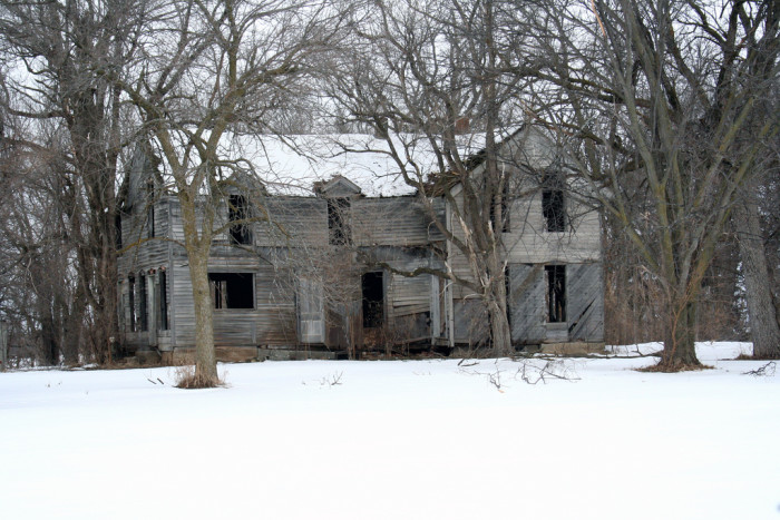 This large derelict home near Fremont looks incredibly desolate sitting empty among the bare trees in the snow.