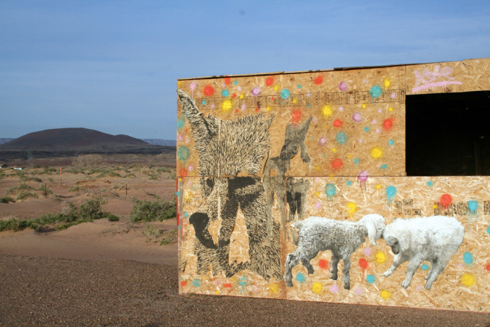 16. A wheat paste of lambs and wolves on the same wall.