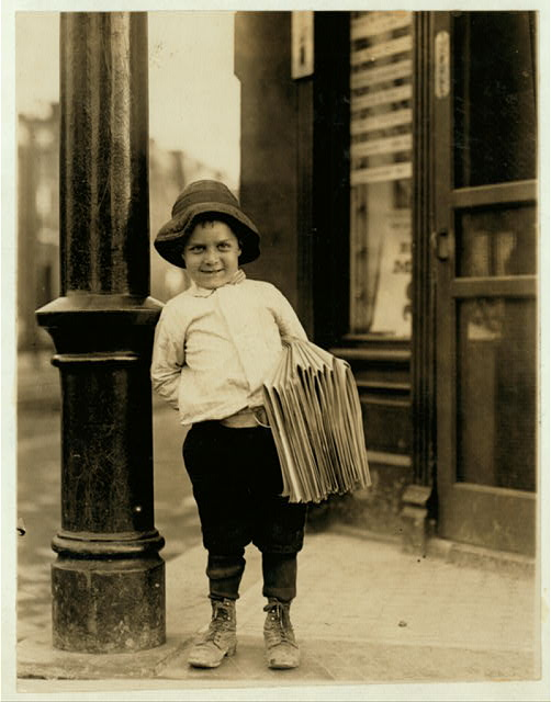 8. Title: Newsboy. Little Fattie. Less than 40 inches high, 6 years old. Been at it one year. May 9th, 1910. Location: St. Louis, Missouri. Creator(s): Hine, Lewis Wickes, 1874-1940, photographer. Date Created/Published: 1910 May 9.
