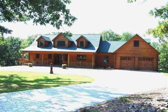 11. 30611 Stonehaven Dr, Warsaw, MO 65355.  Log beams & siding plus stone exterior make this 5 bedroom, 3 bedroom home unique.  For $699,999, you get three fireplaces, wraparound decks and patios, as well as some of the custom built furnishings!