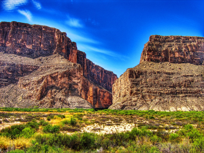 5) The cliffs surrounding the Santa Elena Canyon in Big Bend National Park stand strong and mighty against the contrasting blue sky.