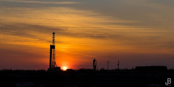 8) A tranquil setting captured in West Texas of the sun fading behind the silhouette of a drilling rig.