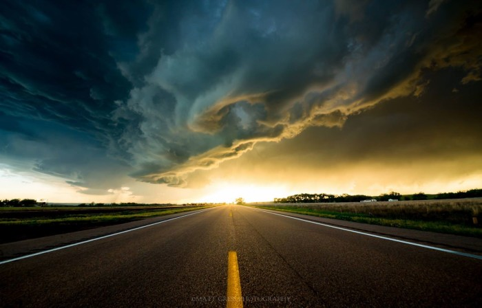 22. Creamy clouds above a lonely road are lit up by a distant sun.