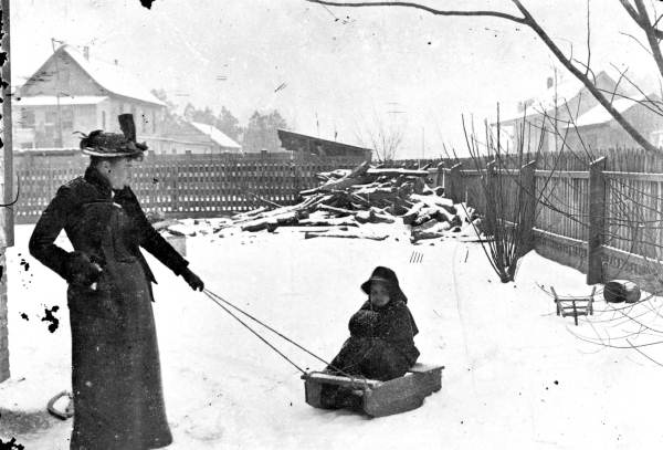 Woman pulling a child on sled in DeLand, 1890