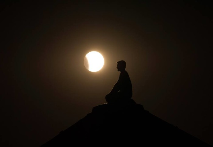 4. An amazing shot of the 2015 supermoon eclipse with a serene figure sitting on top of a grain bin.