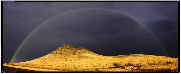 4) A cheerful rainbow illuminating the ominous sky during a thunderstorm in Marfa, TX.