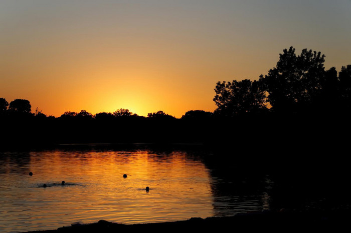 8. Kids play in the water at Wagon Train Lake as the sun gently sets behind them.