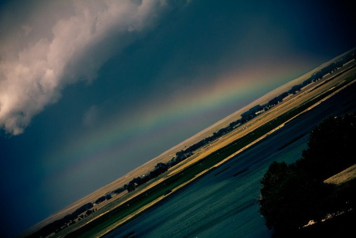 6. An artistic view of a rainbow over water.