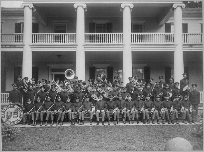 The faces in group photos may change through the ages, but the awkwardness will always remain. Here we have a 1915 photograph of Carlisle Indian School Band seated on steps of a the school building.