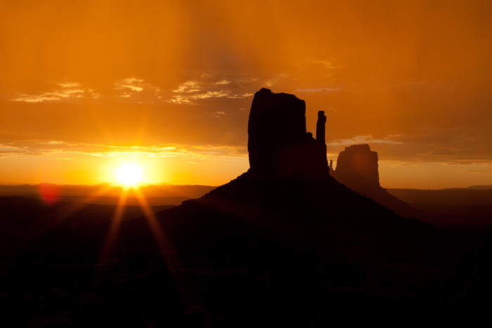 1. Let's start with a picturesque view of Monument Valley just as the sun is peeking over the horizon.