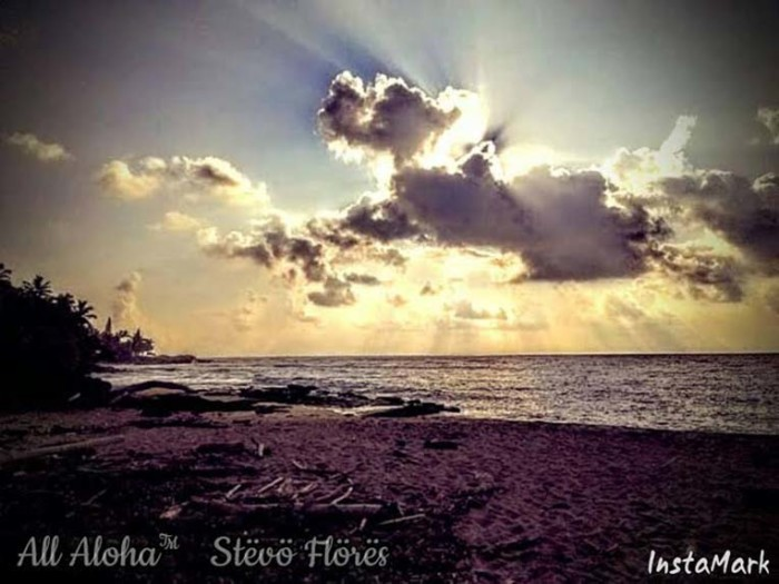 9) Magical is the way the sun filters through the clouds in this photograph of Wailua Beach.