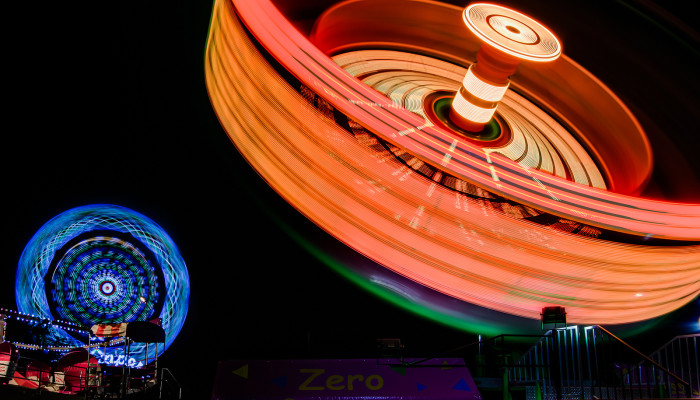 11. A long exposure captures carnival rides in gleeful motion on a clear night.
