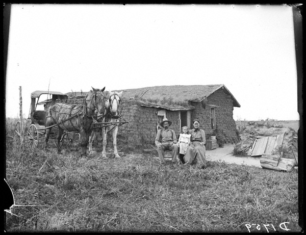 5. A family sits proudly outside of their modest sod home in Sartoria.