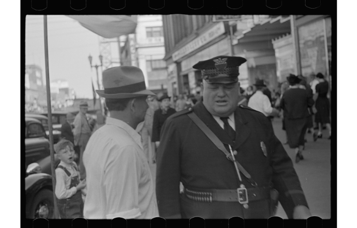 9. A policeman in a crowd on a Lincoln street in 1938.