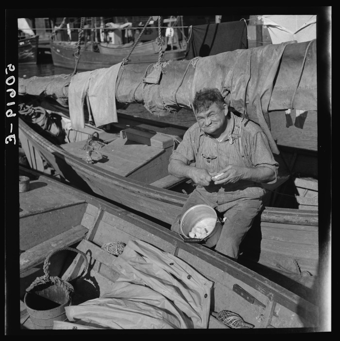 1. The cook on a fishing boat in Charleston peeling potatoes for Christmas dinner. 1938.