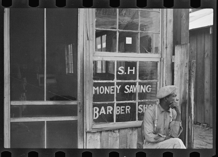 10. A patron waits patiently outside of a Natchez barber shop.