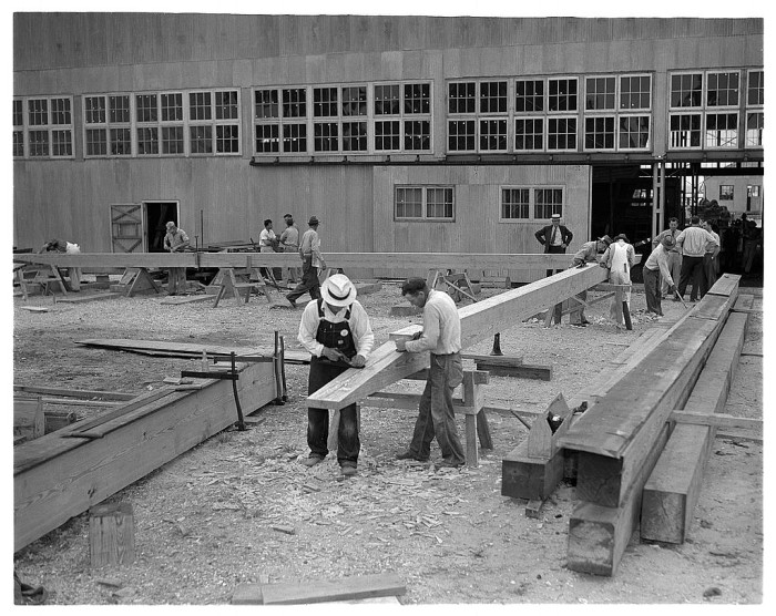 10. In May of 1942, several shipyard workers inspect keel timbers for a new submarine chaser.