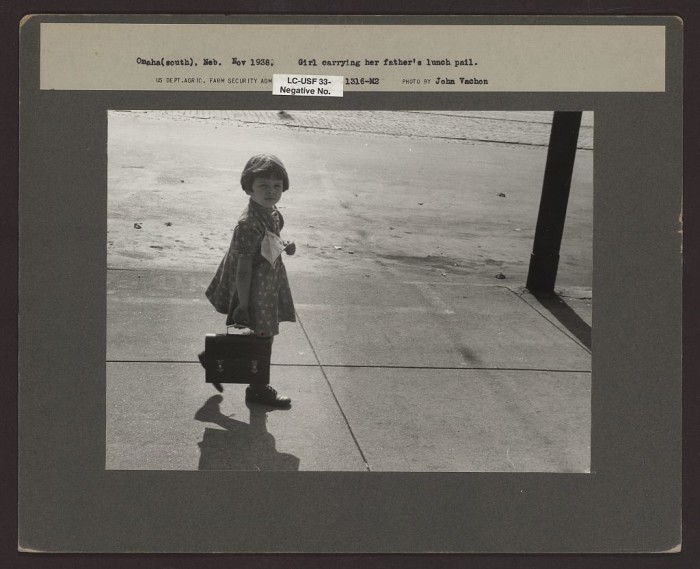 13. A girl carries her father's lunch pail in Omaha.