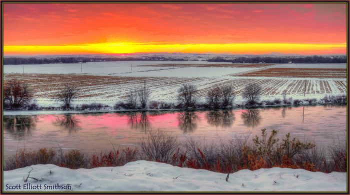 10. The beautiful Snake River reflects a sunset, surrounded by snowy fields.
