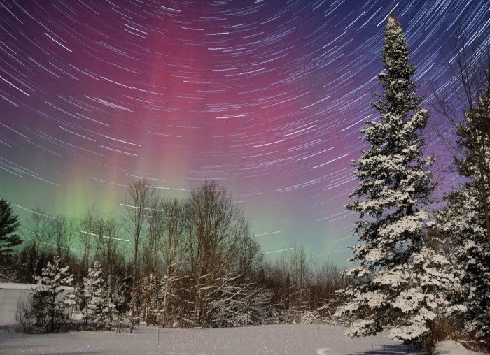11. Another gorgeous, long exposure shot made by stitching several photos together to show the earth's rotation using stars. The Northern Lights stand out from behind.