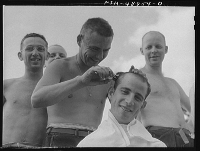 14. A Camp Shelby soldier is given a haircut by his peers in June of 1941.