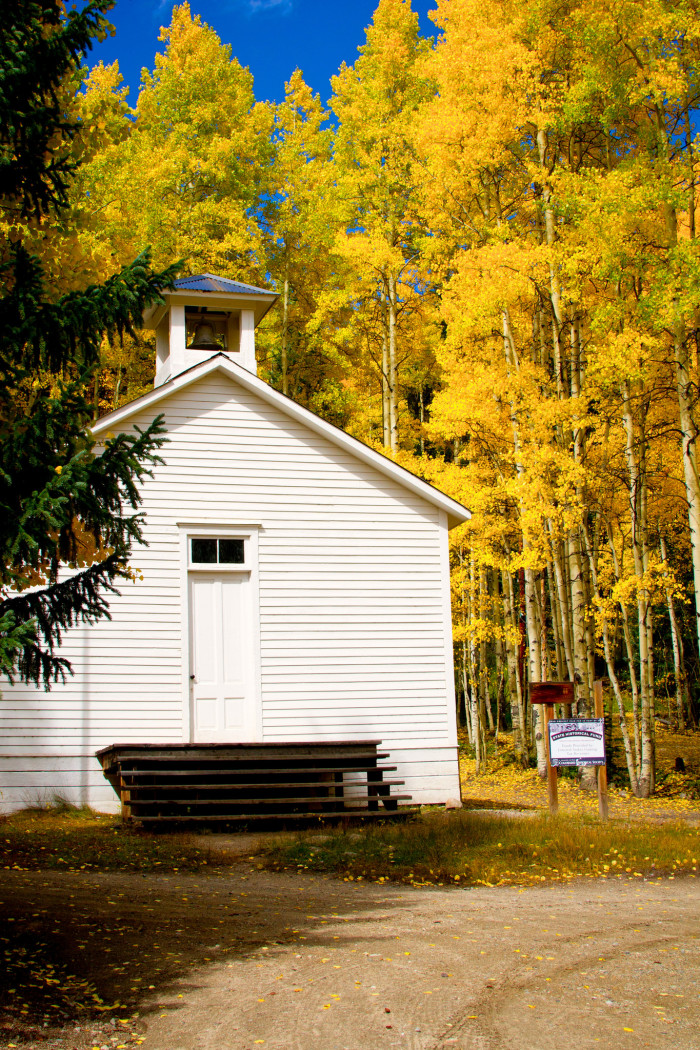 The old one-room school house rests among colorful Aspen trees.