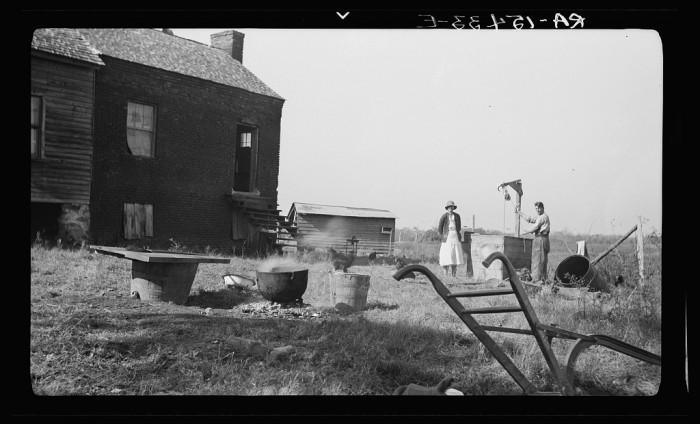 18. In this image, a family is rendering lard in Laurens, SC. 1936.