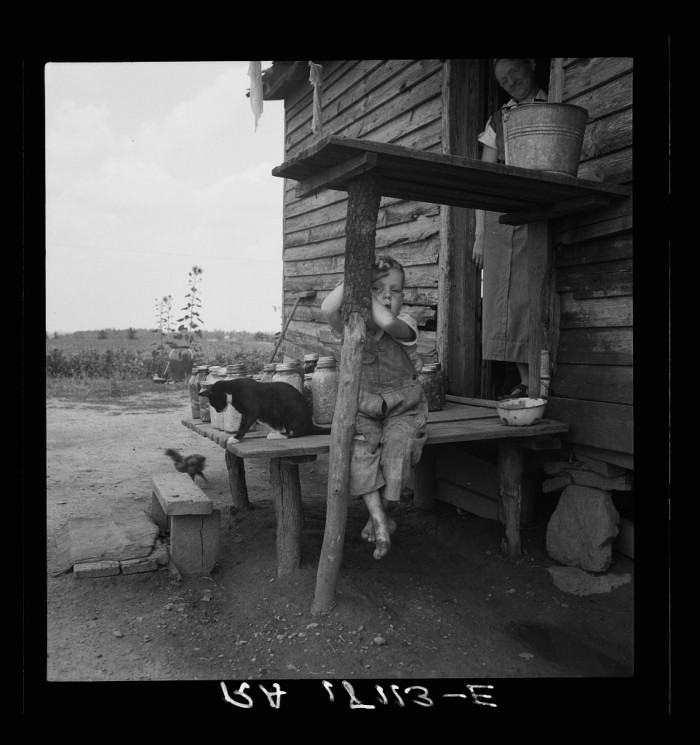 21. A child, a cat and canned food on the porch near Gaffney in 1937.