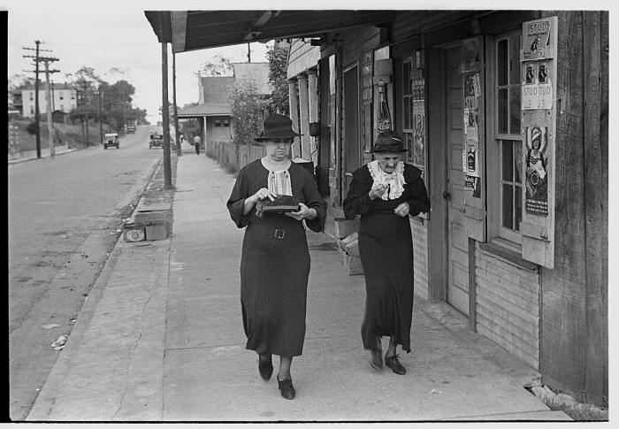 3. Two women stroll along a Natchez street in October of 1935.