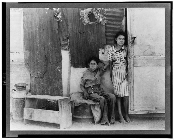 16. These children were part of a migrant cotton laborer family from Mexico sitting outside their home in Casa Grande (1937).