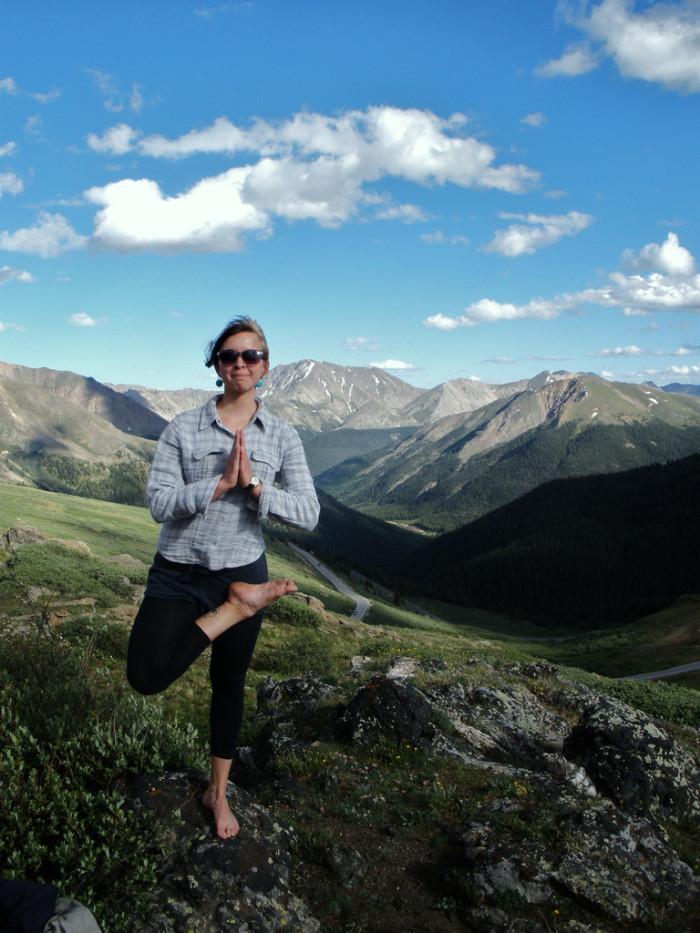5. Practicing yoga atop a mountain.